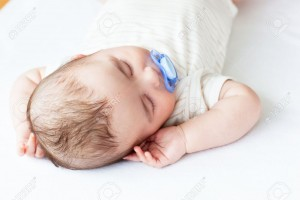 10243732-Portrait-of-an-adorable-baby-with-a-pacifier-sleeping-in-a-bed-Stock-Photo