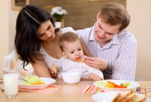 young family at home having meal together with a baby